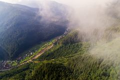 Εναέρια άποψη του χωριού στα Καρπάθια βουνά με τα σύννεφα στο πρώτο πλάνο Στοκ Εικόνες