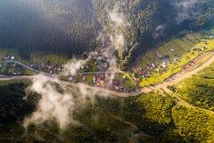 Εναέρια άποψη του χωριού στα Καρπάθια βουνά με τα σύννεφα στο πρώτο πλάνο Στοκ Εικόνα
