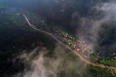 Εναέρια άποψη του χωριού στα Καρπάθια βουνά με τα σύννεφα στο πρώτο πλάνο Στοκ εικόνες με δικαίωμα ελεύθερης χρήσης