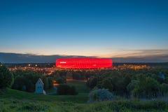 Εναέρια άποψη του χώρου Allianz, το γήπεδο ποδοσφαίρου FC Μπάγερν, που φωτίζεται στο κόκκινο στο σούρουπο φ Στοκ Εικόνα