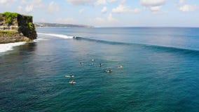 Εναέρια άποψη του surfer που απολαμβάνει τα κύματα στον πίνακά τους, που περιμένει τα κύματα έπειτα ο απότομος βράχος φιλμ μικρού μήκους
