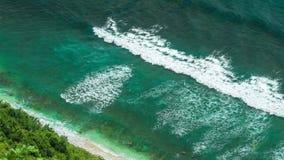 Εναέρια άποψη των κυμάτων που κυλούν ένα προς ένα στην παραλία Nunggalan κοντά σε Uluwatu, Μπαλί, Ινδονησία φιλμ μικρού μήκους