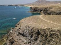 Εναέρια άποψη των οδοντωτών ακτών και των παραλιών Lanzarote, Ισπανία, καναρίνι Κόκκινη λέμβος που δένεται σε έναν όρμο στοκ φωτογραφίες με δικαίωμα ελεύθερης χρήσης