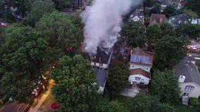 Εναέρια άποψη των πυροσβεστικών οχημάτων και των συσκευών που μάχονται μια πυρκαγιά σπιτιών φιλμ μικρού μήκους