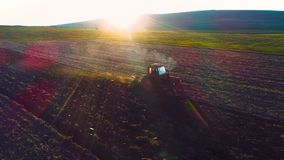 Εναέρια άποψη των τομέων συγκομιδών με την καλλιέργεια του τρακτέρ Farmer που οργώνει τον τομέα καλαμιών φιλμ μικρού μήκους