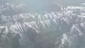 Εναέρια άποψη των χιονωδών βουνών Η άποψη από το αεροπλάνο σε ένα βουνό διπλώνει Οι κορυφές των βουνών που καλύπτονται με το χιόν φιλμ μικρού μήκους