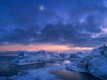 Εναέρια άποψη των χιονωδών βουνών, θάλασσα, ζωηρόχρωμος νεφελώδης ουρανός τη νύχτα στοκ εικόνες