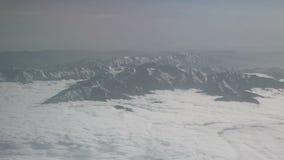 Εναέρια άποψη των χιονωδών βουνών και των σύννεφων Η άποψη από το αεροπλάνο σε ένα βουνό διπλώνει Οι κορυφές των βουνών που καλύπ φιλμ μικρού μήκους