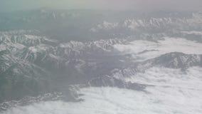Εναέρια άποψη των χιονωδών βουνών και των σύννεφων Η άποψη από το αεροπλάνο σε ένα βουνό διπλώνει Οι κορυφές των βουνών που καλύπ απόθεμα βίντεο
