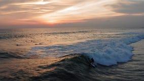 Εναέρια άποψη ωκεάνιου κύματος ηλιοβασιλέματος Surfer του οδηγώντας Ωκεάνιος τρόπος ζωής σερφ κηφήνων πυροβοληθείς 4k, ακραίος αθ απόθεμα βίντεο