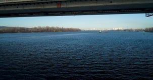 Εναέρια άποψη όχι του ποταμού Dnieper στο Κίεβο Πέταγμα κάτω από τη γέφυρα απόθεμα βίντεο