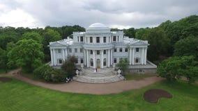 Εναέρια έρευνα για τη νύφη και το νεόνυμφο που χορεύουν στο παλάτι στον κήπο Μεγάλη άσπρη άποψη παλατιών ή κάστρων Να πετάξει απόθεμα βίντεο