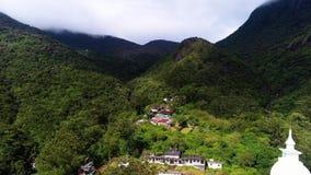 Εναέρια κινηματογράφηση σε πρώτο πλάνο από την κορυφή της τακτοποίησης με το ναό στα βουνά της αιχμής του Adam στη Σρι Λάνκα φιλμ μικρού μήκους