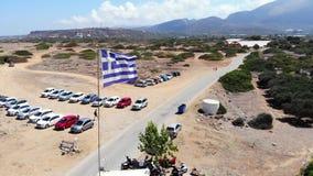 Εναέρια μύγα γύρω από τη σημαία της Ελλάδας που κυματίζει στον αέρα θάλασσας, Κρήτη φιλμ μικρού μήκους
