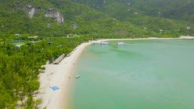 Εναέρια πράσινα βουνά άποψης στο τροπικό νησί και το πλέοντας σκάφος Όμορφο πράσινο νησί και αμμώδης παραλία στην ακτή, σκάφη φιλμ μικρού μήκους