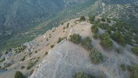 Εναέρια πτήση πέρα από το νέο ζεύγος που στέκεται πεζοπορία και το ταξίδι σειράς βουνών ακρών απότομων βράχων στην επικά αλπικά ρ φιλμ μικρού μήκους