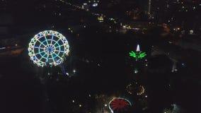 Εναέρια πυροβοληθε'ντα φω'τα πόλεων νύχτας λούνα παρκ συνδετήρας Εναέριο κινούμενο μέτωπο άποψης της όμορφης ρόδας Ferris στο υπό απόθεμα βίντεο