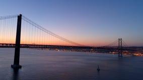 Εναέρια σκιαγραφία μήκους σε πόδηα της γέφυρας της 25ης Απριλίου στο λυκόφως απόθεμα βίντεο