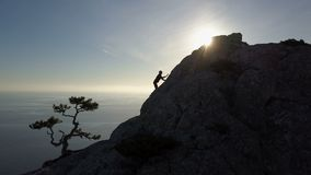 Εναέρια σκιαγραφία της νέας αναρρίχησης γυναικών μέχρι την κορυφή ενός βουνού μπροστά από τη θάλασσα Πτήση πέρα από την κυρία φιλμ μικρού μήκους