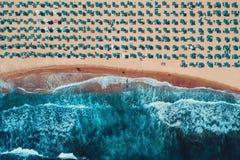 Εναέρια τοπ άποψη σχετικά με την παραλία Ομπρέλες, κύματα άμμου και θάλασσας στοκ εικόνα