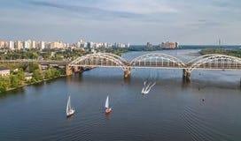 Εναέρια τοπ άποψη της γέφυρας, των γιοτ και των βαρκών Darnitsky που πλέουν στον ποταμό Dnieper άνωθεν, ορίζοντας πόλεων του Κίεβ Στοκ εικόνα με δικαίωμα ελεύθερης χρήσης