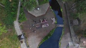 Εναέρια τοπ άποψη της γαμήλιας τελετής με την αψίδα και τους φιλοξενουμένους που κάθονται στις καρέκλες, στην όχθη ποταμού απόθεμα βίντεο