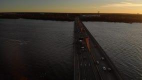 Εναέρια cinematic μύγα ηλιοβασιλέματος πέρα από μια νότια γέφυρα στη Ρήγα, Λετονία - χρυσός πυροβολισμός κηφήνων ώρας επαγγελματι απόθεμα βίντεο