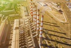 Εναέριες ηλεκτρικές εγκαταστάσεις δύναμης με τους υψηλούς βιομηχανικούς σωλήνες σε ένα καλοκαίρι ημέρα φ στοκ εικόνα