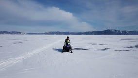 Εναέριος γύρος οχημάτων για το χιόνι άποψης στην παγωμένη λίμνη Baikal το χειμώνα απόθεμα βίντεο