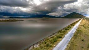 Εναέριος δρόμος άποψης που διασχίζει στο υπόβαθρο βουνών τοπίων φραγμάτων Στοκ Φωτογραφίες