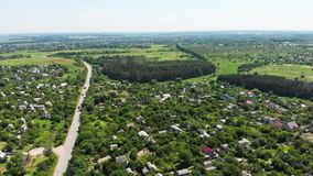 Εναέριος κηφήνας που πυροβολείται μιας δορυφορικής άποψης του χωριού προαστιακής σταυροδρομιών απόθεμα βίντεο