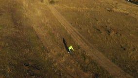 Εναέριος κινηματογράφος κηφήνων 4k Πέταγμα κατά μήκος ενός ατόμου που οδηγά το ποδήλατό του κάτω υπαίθρια απόθεμα βίντεο