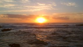 Εναέριος πυροβολισμός ηλιοβασιλέματος που πετά προς τη ρύθμιση του ήλιου πέρα από τον ωκεανό με τις πορτοκαλιές αντανακλάσεις στο φιλμ μικρού μήκους