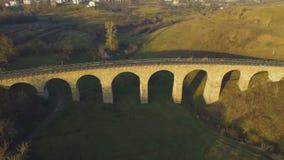 Εναέριος πυροβολισμός της γέφυρας σιδηροδρόμων πετρών στο ηλιοβασίλεμα με την ενδιαφέρουσα σκιά 4k φιλμ μικρού μήκους