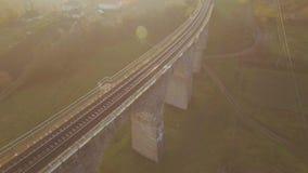 Εναέριος πυροβολισμός της γέφυρας σιδηροδρόμων πετρών στο ηλιοβασίλεμα με την ενδιαφέρουσα σκιά 4k απόθεμα βίντεο