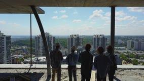 Εναέριος πυροβολισμός της ομάδας οικοδόμων στην πλάτη εργοτάξιων οικοδομής οπισθοσκόπο του εργάτη που συζητά το σχέδιο του προγρά απόθεμα βίντεο