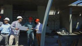 Εναέριος πυροβολισμός της ομάδας οικοδόμων στο εργοτάξιο οικοδομής που συζητά το σχέδιο του προγράμματος με τη χρησιμοποίηση αρχι απόθεμα βίντεο