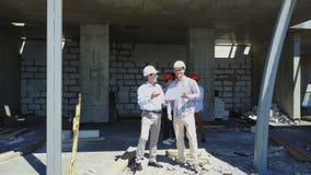 Εναέριος πυροβολισμός της ομάδας οικοδόμων στο εργοτάξιο οικοδομής που συζητά το σχέδιο του προγράμματος με τη χρησιμοποίηση αρχι φιλμ μικρού μήκους