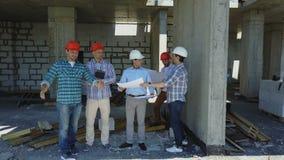 Εναέριος πυροβολισμός της ομάδας οικοδόμων στο εργοτάξιο οικοδομής που συζητά το σχέδιο του προγράμματος με τον αρχιτέκτονα απόθεμα βίντεο