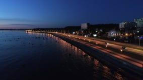 Εναέριος πυροβολισμός της σκηνής με το Drive των αυτοκινήτων στο δρόμο ακτών στη νύχτα απόθεμα βίντεο
