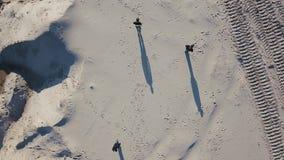 Εναέριος πυροβολισμός Τρία άτομα αποκλίνουν στις πλευρές στην έρημο Ο ήλιος ρίχνει τις σκιές στην άμμο Τοπ όψη φάρμακο φιλμ μικρού μήκους