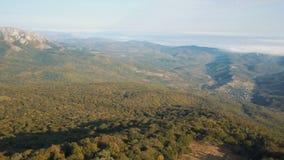 Εναέριος πυροβολισμός των όμορφων βουνών που καλύπτονται από τη δασική πτήση φθινοπώρου επάνω από τα βουνά στο ηλιοβασίλεμα Τα σύ φιλμ μικρού μήκους