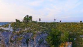 Εναέριος πυροβολισμός ενός ηλιοβασιλέματος κοντά στους βράχους Τα ζωηρά χρώματα απεικονίζονται στο νερό απόθεμα βίντεο