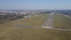 Εναέριος πυροβολισμός ενός μικρού αεροπλάνου προωστήρων που πετά κοντά στο διάδρομο αερολιμένων πόλεων μια ηλιόλουστη ημέρα 4K βί φιλμ μικρού μήκους
