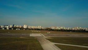 Εναέριος πυροβολισμός ενός μικρού αεροπλάνου προωστήρων που προσγειώνεται στο διάδρομο αερολιμένων πόλεων μια ηλιόλουστη ημέρα 4K απόθεμα βίντεο