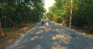Εναέριος πυροβολισμός του άνδρα και της γυναίκας που τρέχουν μαζί στο πάρκο φιλμ μικρού μήκους