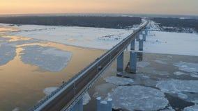 Εναέριο ακολουθώντας πυροβοληθε'ν μόνο αυτοκίνητο που διασχίζει τη γέφυρα πέρα από το χειμερινό ποταμό με τους επιπλέοντες πάγους απόθεμα βίντεο