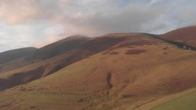 Εναέριο αριστερό sideway μήκος σε πόδηα mountainside με μια misty σύνοδο κορυφής κ φιλμ μικρού μήκους