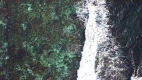Εναέριο βίντεο κηφήνων των όμορφων κυμάτων θάλασσας που συντρίβουν στο σκόπελο εμποδίων απόθεμα βίντεο