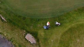 Εναέριο γήπεδο του γκολφ άποψης Οι παίκτες γκολφ που περπατούν κάτω από τη στενή δίοδο σε μια σειρά μαθημάτων με το γκολφ τοποθετ Στοκ φωτογραφία με δικαίωμα ελεύθερης χρήσης
